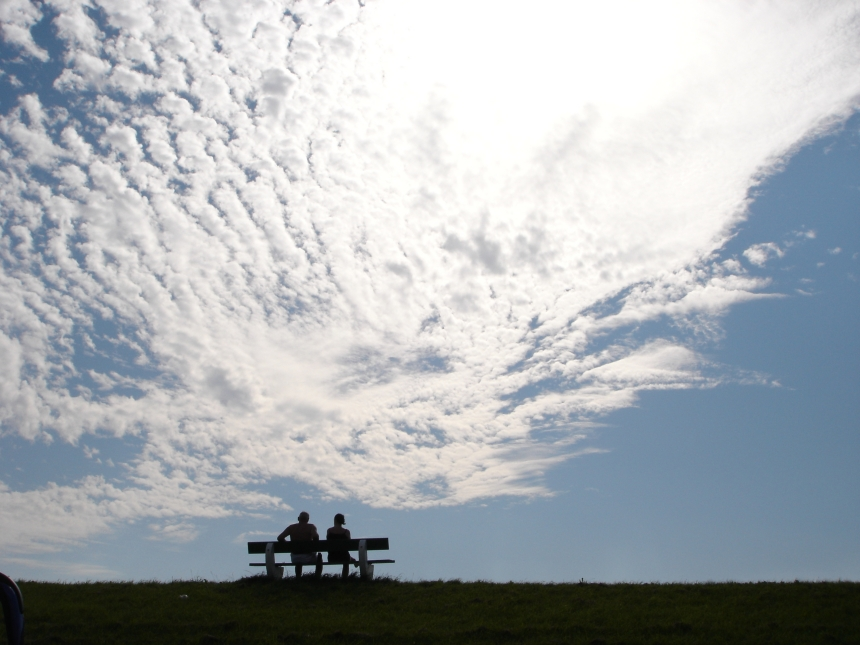 two people sat next to each other on a bench under a sunny and cloudy sky