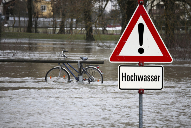 symbolic picture, bicycle is under water because of high water, sign warns of high water