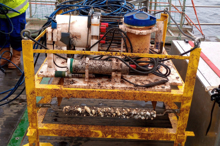 A dirty yellow steel frame with sensors partly covered with mussels.